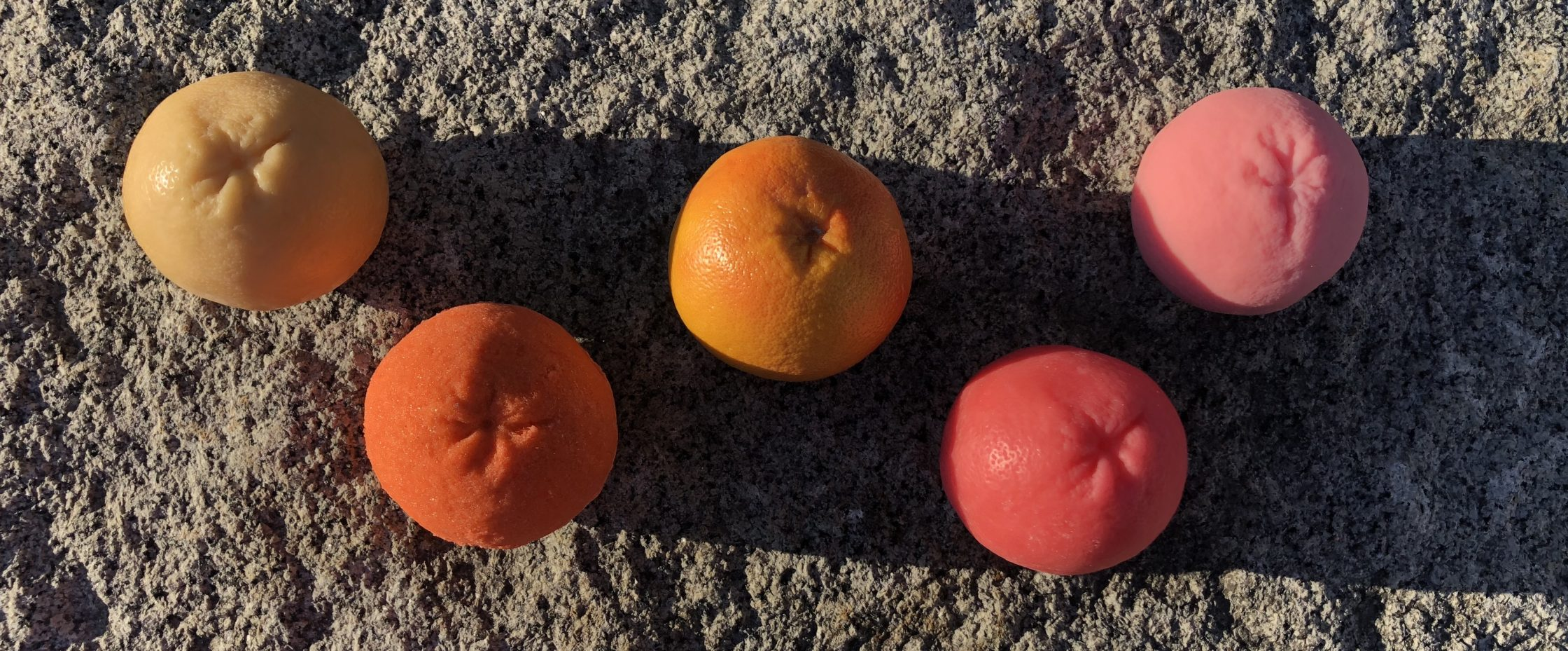 wax, rubber, sugar grapefruits in evening light on stone